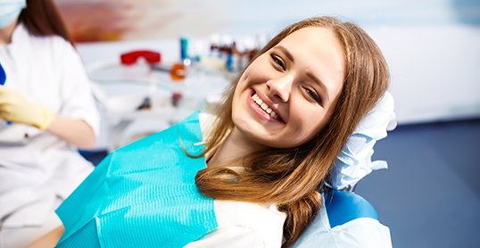 Stock image of girl smiling in a dental exam chair