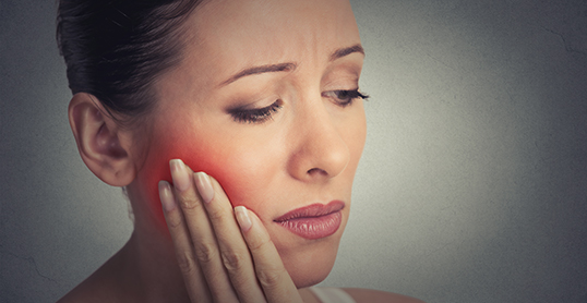Stock image of a woman with root canal pain